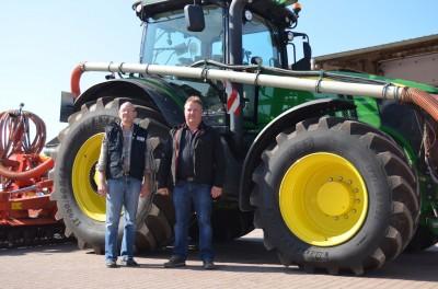 Dietmar Hülsmann (re.) und Rainer Fischer vor einem Schlepper John Deere mit BKT-Reifen Agrimax Force