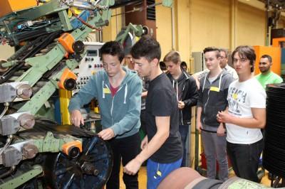 Ein Schüler und Christopher Weber (Pirelli) beim Schneiden von gummiertem Reifenkarkassgewebe